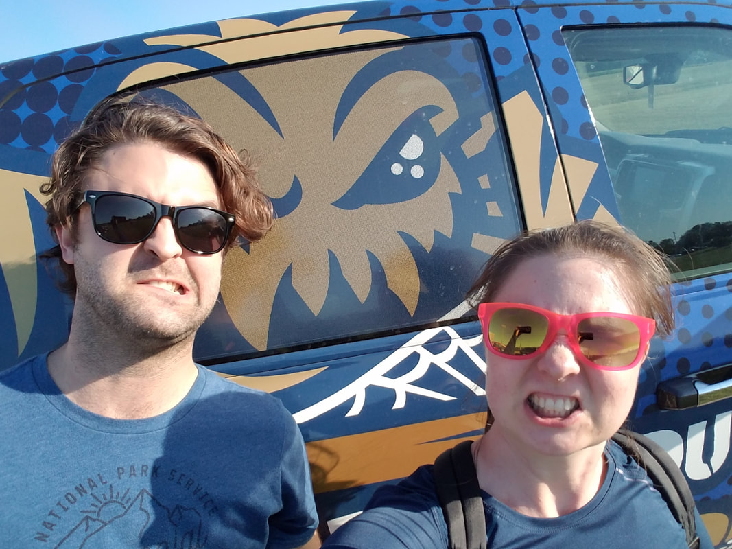 Wyatt and Cathlyn, in sunglasses, stand in front of a mural of a grimacing spider mascot. Wyatt and Cathlyn try to match the spider's fierce expression with moderate success. (Twenty Questions with Wyatt Kent, Compass Creative Dramatics Artistic Director)
