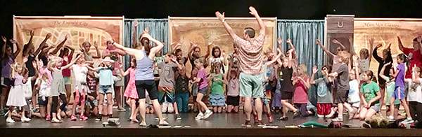 Children learn dance moves from instructors David Smith and Cathlyn Melvin during theatre camp, Why Small Business? Small Business Saturday at Compass Creative Dramatics