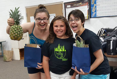 A student in Columbus, Wisconsin poses, wearing her Wizard of Oz t-shirt, with teachers Cathlyn Melvin and Cassandra Quinn, who hold the pineapples they received as teacher gifts.
